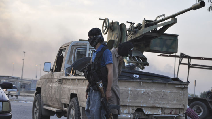 2014: Islamic State militants stand guard at a checkpoint after capturing Mosul