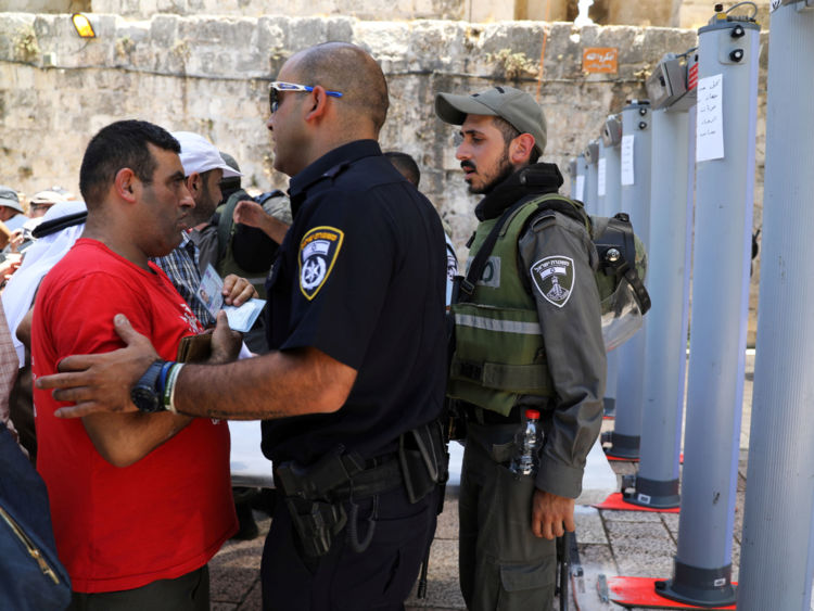 An Israeli police officer checks the identity of a Palestinian man next to newly installed metal detectors at an entrance to the compound known to Muslims as Noble Sanctuary and to Jews as Temple Mount, in Jerusalem's Old City July 16, 2017. REUTERS/Ammar Awad