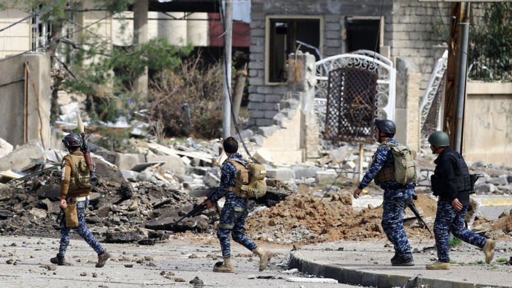 Federal police officers carry weapons as the offensive pushes into the Old City in the west of Mosul