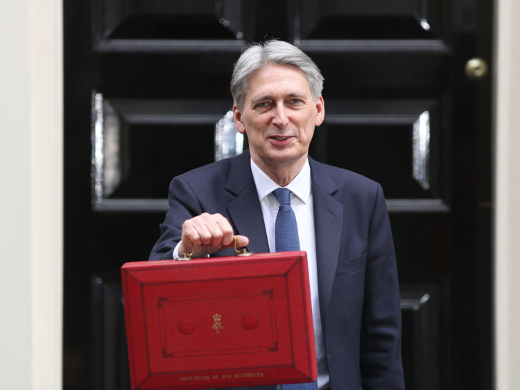 Chancellor of the Exchequer Philip Hammond holds the budget box up to the media as he leaves 11 Downing Street on March 8, 2017 in London, England