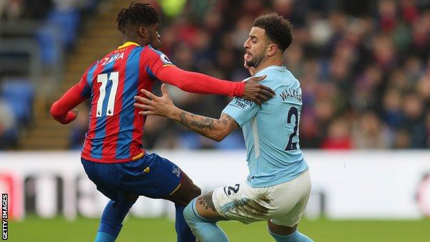 Kyle Walker (right) challenges Wilfried Zaha