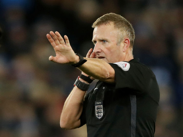 Referee Jonathan Moss awaits a decision from VAR at a Leicester City/Fleetwood Town game