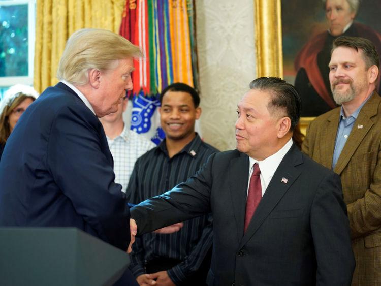 U.S. President Donald Trump shakes hands with Hock E. Tan, CEO of Broadcom