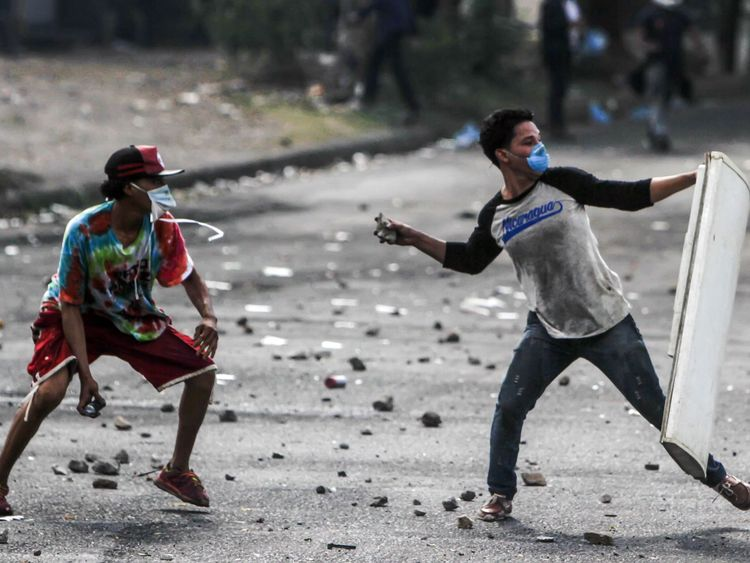 Students throw stones as they clash with police