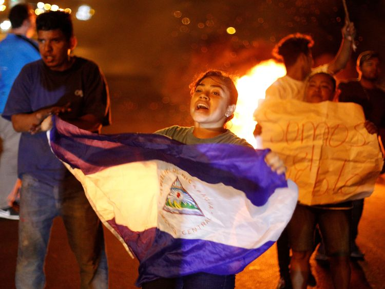 A demonstrator holds up a Nicaragua flag next to a burning barricade