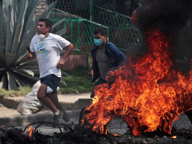 Demonstrators run past a burning barricade