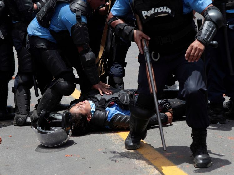 A riot policeman lies injured