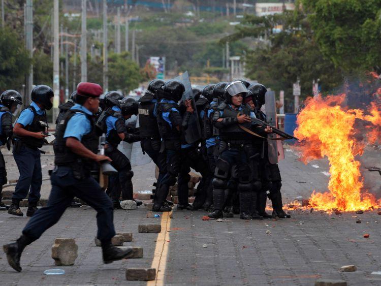 A petrol bomb explodes near riot policemen