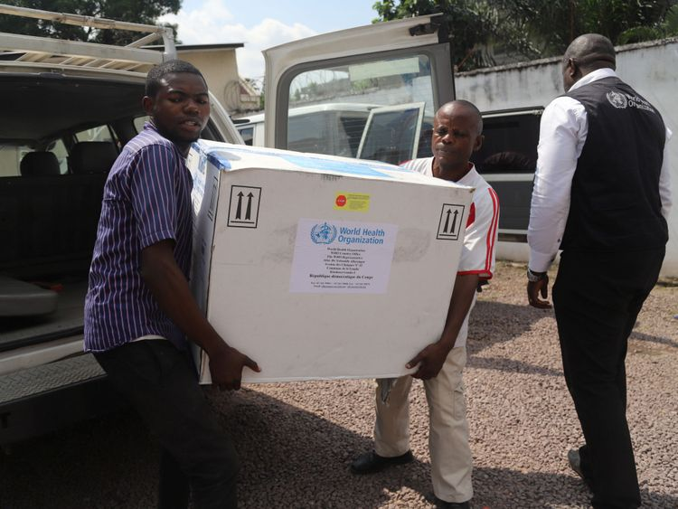 Congolese Health Ministry officials carry the first batch of experimental Ebola vaccines in Kinshasa