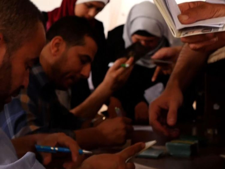 Palestinians try to get their documents in order so they can have a chance to get on a bus to Egypt