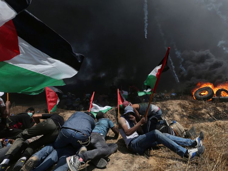 Palestinian demonstrators take cover from Israeli fire and tear gas during a protest against U.S. embassy move to Jerusalem and ahead of the 70th anniversary of Nakba, at the Israel-Gaza border in the southern Gaza Strip May 14, 2018