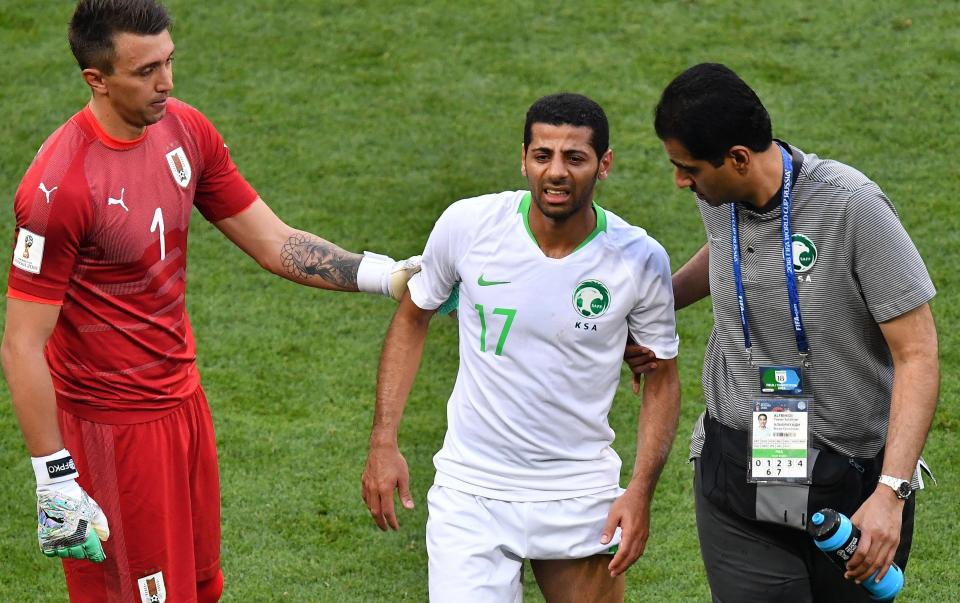 Taiseer Al Jassam goes off injured against Uruguay.