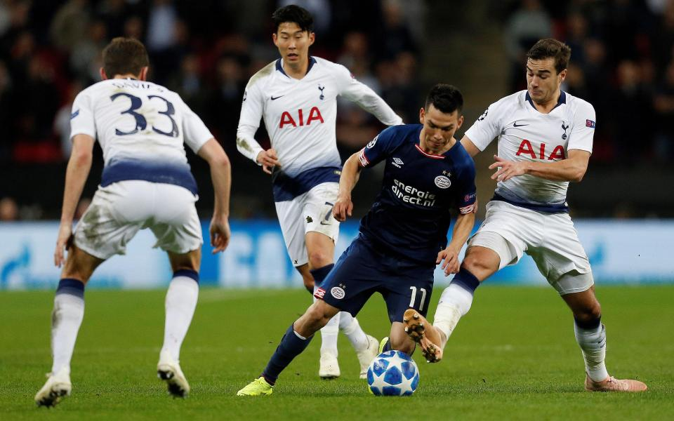 PSV Eindhoven star Hirving Lozano attempts to evade Tottenham challenges.