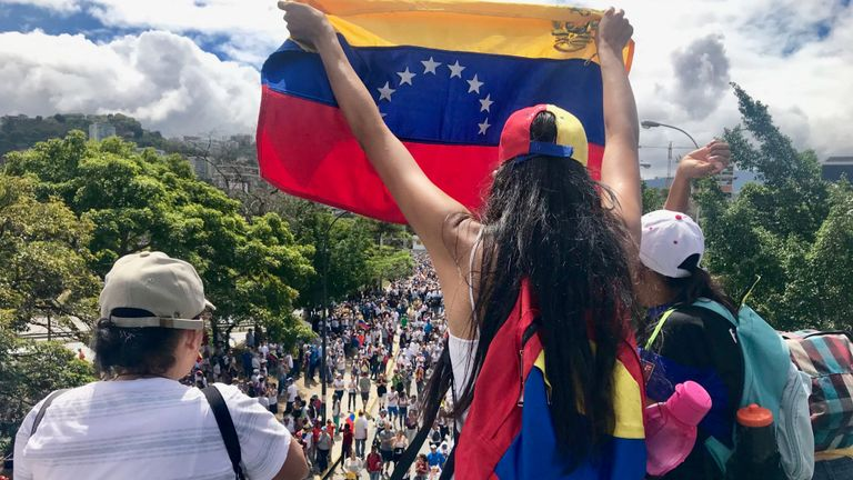 A woman waves a Venezuelan flag as people pass under the bridge