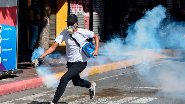 An opposition demonstrator runs with a tear gas canister