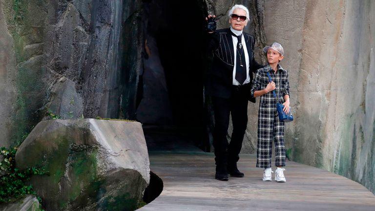 The fashion designer walks with his godson Hudson Kroenig during a 2018 Chanel show