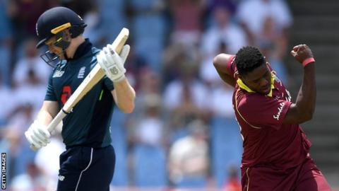 England captain Eoin Morgan (left) looks dejected as he walks off after being dismissed by Oshane Thomas (right) who swings his arm in celebration