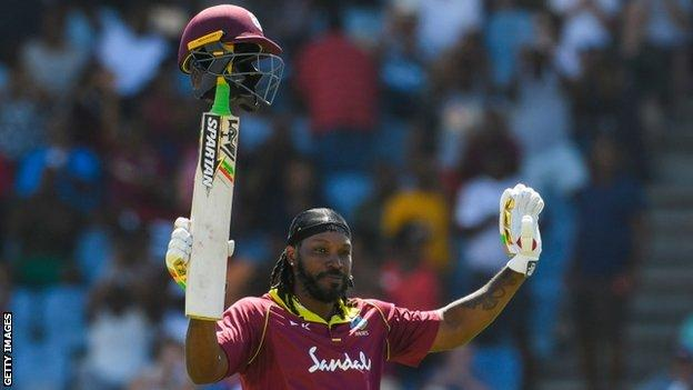West Indies opener Chris Gayle lifts his helmet on the handle of his bat and waves to the crowd in celebration of his half-century against England in the fifth ODI