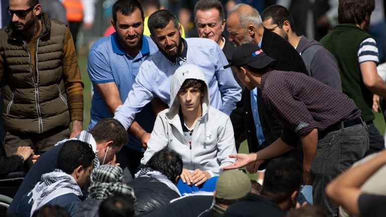Zaid Mustafa (C, in wheelchair), who was wounded in the attacks arrives for prayers