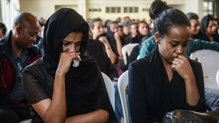 People mourn during a memorial service for the crew members who died in the accident