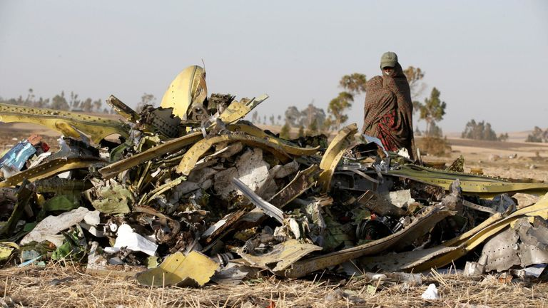 A woman stands near a pile of debris from the Ethiopian Airlines wreckage