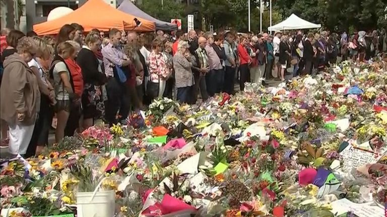 Mourners gather and leave flowers as a nation remembers the victims