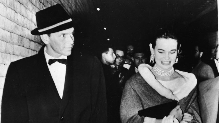 Gloria Vanderbilt walks alongside American singer and actor Frank Sinatra