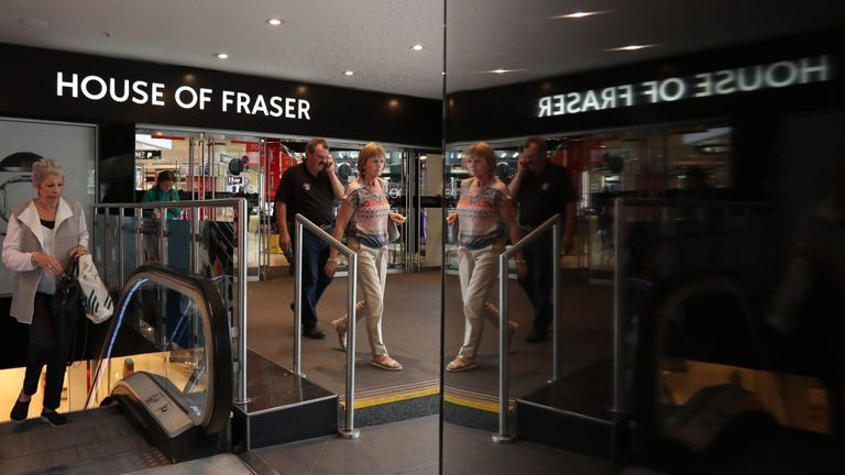 People walk by the entrance to the retail store House of Fraser in central London