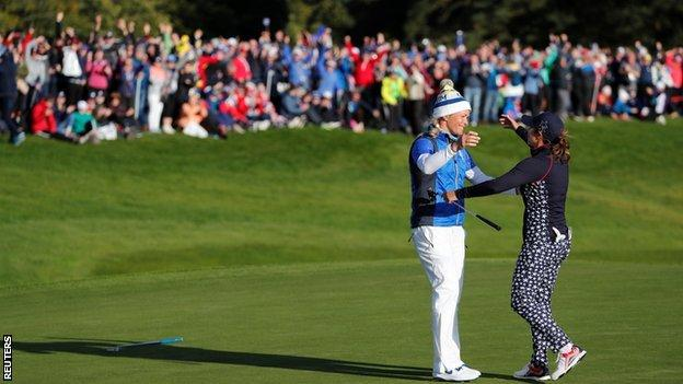 Suzann Pettersen consoles opponent Marina Alex on the 18th green after rolling in the putt to win the Solheim Cup