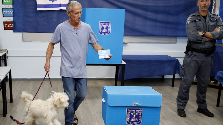 An Israeli man holds his dog while casting his ballot during Israel's parliamentary election at a polling station in Rosh Haayin, on September 17, 2019. (Photo by Jack GUEZ / AFP)        (Photo credit should read JACK GUEZ/AFP/Getty Images)