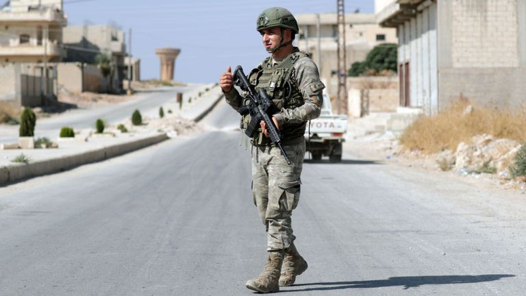 A Turkish solider patrols in the town of Tal Abyad, Syria
