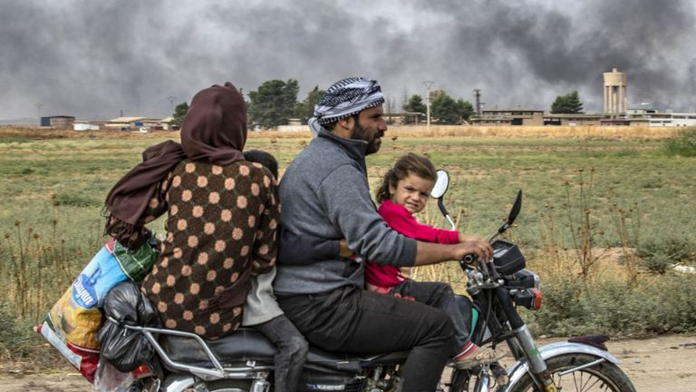 """Members of a Syrian family use a motorcycle to flee the countryside of the northeastern Syrian town of Ras al-Ain on the Turkish border, toward the west to the town of Tal Tamr on October 19, 2019. The smoke behind them is from burning tyres used to impede visibility from warplanes. - Turkey's President Recep Tayyip Erdogan fired off a fresh warning today to """"crush"""" Kurdish forces as both sides traded accusations of violating a US-brokered truce deal in northeastern Syria. (Photo by Delil SOULEI"""