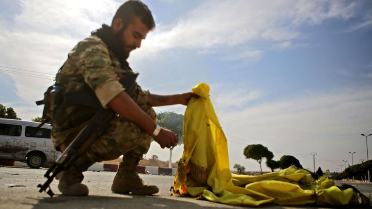 A Turkish-backed Syrian fighter burns the flag of the Syrian Democratic Forces (SDF) in the town of Ayn al-Arus, south of the border town of Tal Abyad, on October 14, 2019, as Turkey and its allies continue their assault on Kurdish-held border towns in northeastern Syria. - Syrian regime forces moved towards the Turkish border after Damascus reached a deal with beleaguered Kurdish forces following a US withdrawal announcement, AFP correspondents reported. (Photo by Bakr ALKASEM / AFP) (Photo by