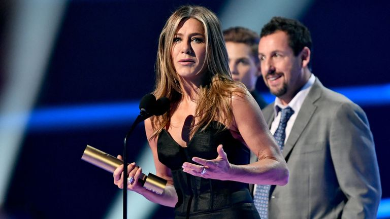 Jennifer Aniston, winner of the People's Icon award, and Adam Sandler on stage during the 2019 E! People's Choice Awards held at the Barker Hangar on November 10, 2019. pIC: E! Entertainment