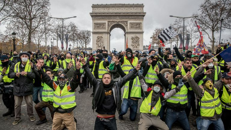 PARIS, FRANCE - DECEMBER 08: Protesters chant slogans during the 'yellow vests' demonstration on the Champs-Elysées near the Arc de Triomphe on December 8, 2018 in Paris France. ''Yellow Vests' ('Gilet Jaunes' or 'Vestes Jaunes') is a protest movement without political affiliation which was inspired by opposition to a new fuel tax. After a month of protests, which have wrecked parts of Paris and other French cities, there are fears the movement has been infiltrated by 'ultra-violent' protesters. Today's protest has involved at least 5,000 demonstrators gathering in the Parisian city centre with police having made over 200 arrests so far.  (Photo by Chris McGrath/Getty Images)