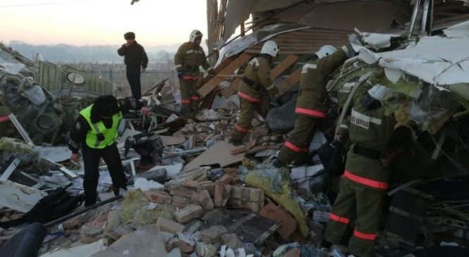Plane crashes into building with almost 100 people on board
