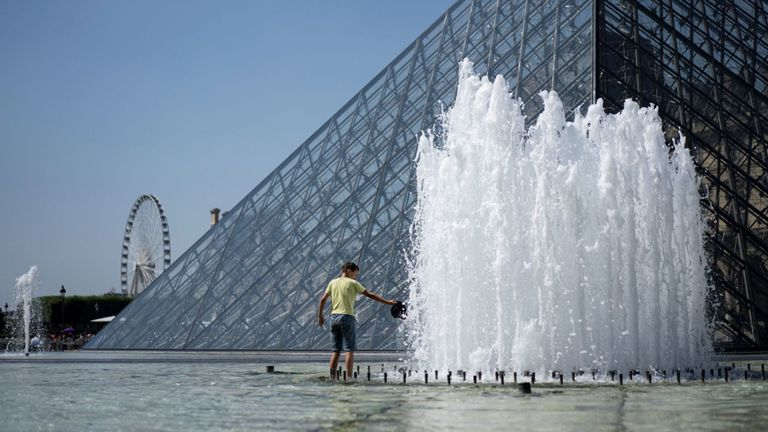 A child refreshes himself in the fountain of the Louvre Pyramid in Paris