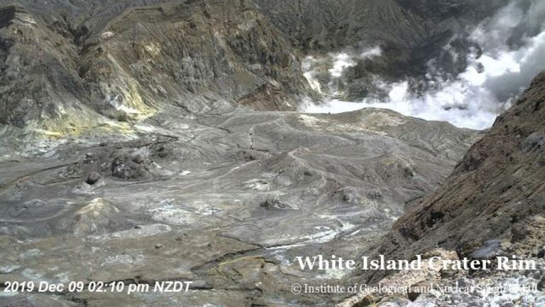 A webcam showed people (centre of picture) hiking in the crater just moments before the eruption
