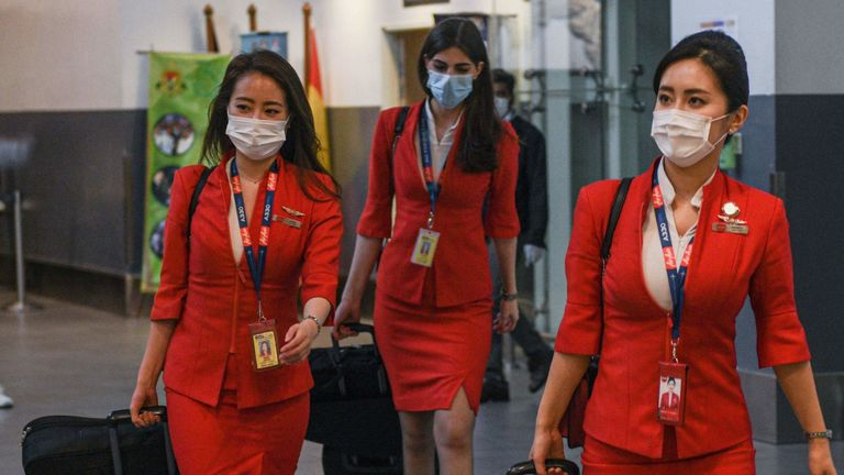 Air Asia flight attendants arrived in Kuala Lumpur wearing face masks