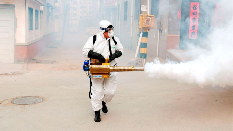 A worker in protective suit disinfects the Dongxinzhuang village in Shandong province