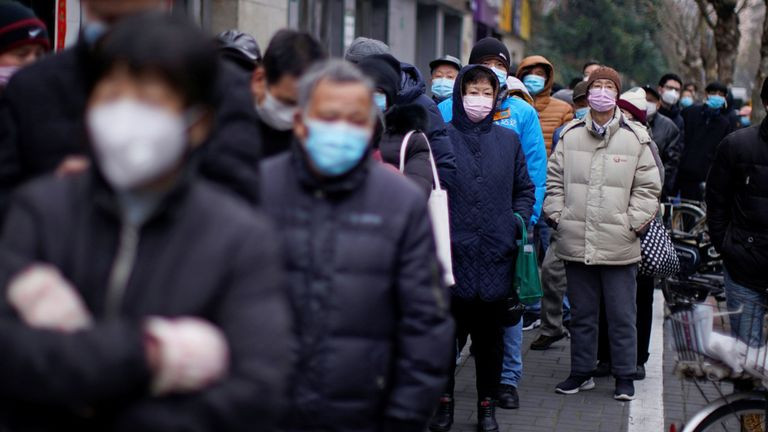People line up outside a drugstore to buy masks in Shanghai