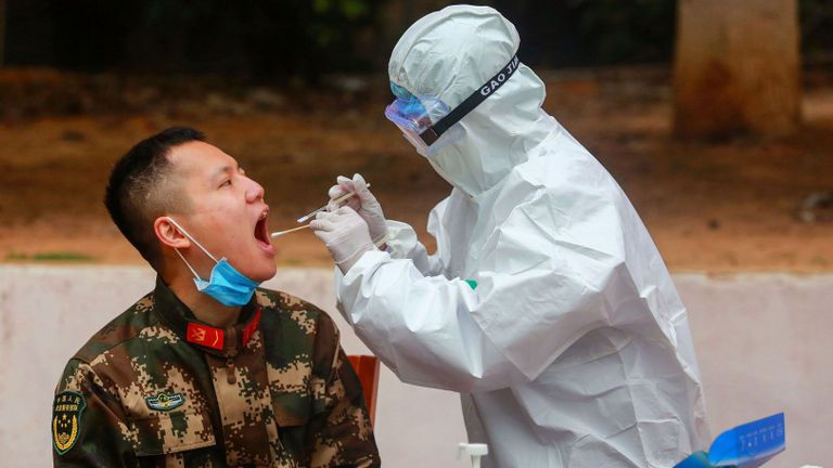 This photo taken on February 11, 2020 shows medical staff members (R) collecting samples from Chinese paramilitary police officers to be tested for the COVID-19 coronavirus as he returns from holidays in Shenzhen in China's southern Guangdong province. - The number of fatalities from China's new coronavirus epidemic jumped to 1,113 nationwide on February 12 after another 97 deaths were reported by the national health commission. (Photo by STR / AFP) / China OUT (Photo by STR/AFP via Getty Images)