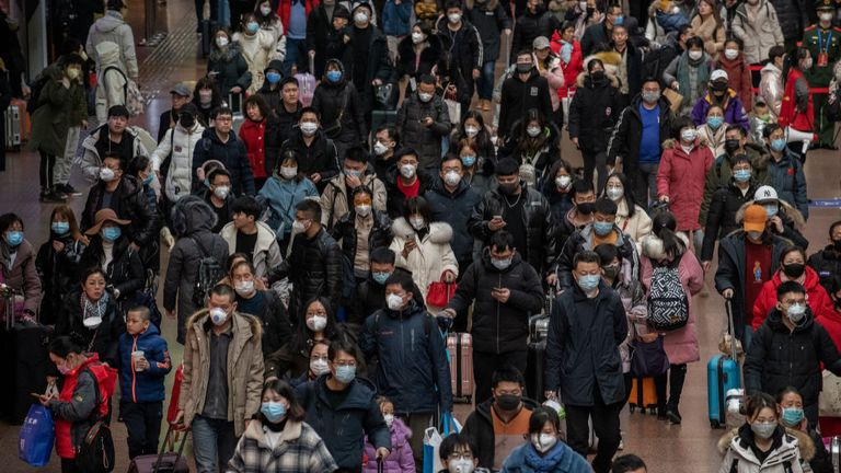 Chinese passengers, most wearing masks, arrive to board trains before the annual Spring Festival at a Beijing railway station