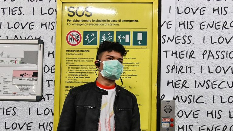 A man wearing a respiratory mask looks on in the subway, in Milan, on February 23, 2020. - Tens of thousands of Italians prepared for a weeks-long quarantine in the country's north on February 23 as nerves began to fray among the locals faced with new lockdown measures