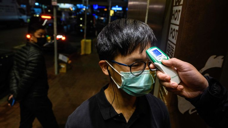A restaurant worker has his temperature taken in Hong Kong