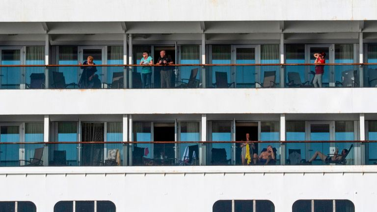 Passengers are seen onboard Holland America's cruise ship Zaandam as it entered the Panama City bay to be assisted by the Rotterdam cruise ship with supplies, personnel and COVID-19 testing devices, eight milles off the coast of Panama City, on March 27, 2020. - Four passengers have died aboard a cruise ship carrying scores of people with flu-like symptoms that has been stranded off the Pacific coast of South America for several days, the liner company said Friday. The Zaandam, with 1,800 passengers on board, is currently in Panama's territorial waters, having been prevented from docking in several countries due to coronavirus fears. (Photo by Ivan PISARENKO / AFP) / The erroneous mention[s] appearing in the metadata of this photo by Ivan Pisarenko has been modified in AFP systems in the following manner: [Ivan Pisarenko] instead of [Luis Acosta]. Please immediately remove the erroneous mention[s] from all your online services and delete it (them) from your servers. If you have been authorized by AFP to distribute it (them) to third parties, please ensure that the same actions are carried out by them. Failure to promptly comply with these instructions will entail liability on your part for any continued or post notification usage. Therefore we thank you very much for all your attention and prompt action. We are sorry for the inconvenience this notification may cause and remain at your disposal for any further information you may require. (Photo by IVAN PISARENKO/AFP via Getty Images)