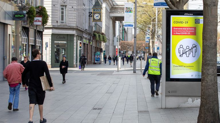 A pedestrian passes a poster alerting the public that if they must leave their home, they must stay within a two kilometre or 20 minute walking distance radius of their home, in Dublin city centre on April 8, 2020, as life in Ireland continues during the nationwide lockdown to combat the novel coronavirus pandemic. - Irish police set up nationwide traffic checkpoints on Wednesday, armed with new powers to enforce a lockdown designed to stem the spread of the coronavirus. Emergency legislation passed in the Irish parliament two weeks ago allows the government to curb non-essential travel during the crisis. People violating the ban risk a fine of up to 2,500 euros ($ 2,700) and/or six months in prison. The roadblocks have been put in place ahead of Easter holidays, traditionally used as an occasion for travel in Ireland. (Photo by PAUL FAITH / AFP) (Photo by PAUL FAITH/AFP via Getty Images)