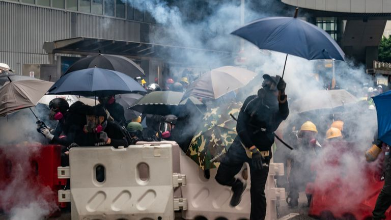 """HONG KONG, CHINA - AUGUST 31:  Protesters throw tear gas canisters back at police during an anti-government rally outside of Central Government Complex on August 31, 2019 in Hong Kong, China. Pro-democracy protesters have continued rallies on the streets of Hong Kong against a controversial extradition bill since 9 June as the city plunged into crisis after waves of demonstrations and several violent clashes. Hong Kong's Chief Executive Carrie Lam apologized for introducing the bill and declared it """"dead"""", however protesters have continued to draw large crowds with demands for Lam's resignation and completely withdraw the bill. (Photo by Anthony Kwan/Getty Images)"""