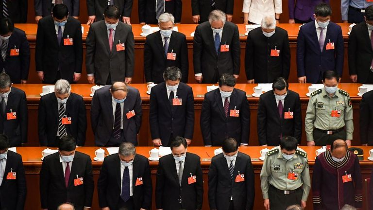 Delegates stand in silent tribute for victims of the COVID-19 during the opening session of the Chinese People's Political Consultative Conference (CPPCC)