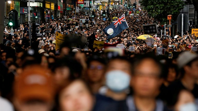 The colonial flag of Hong Kong is held aloft during a march by protesters